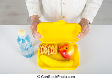 The schoolboy holding a yellow box with lunch in school.