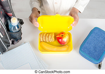 The schoolboy holding a yellow plastic box with lunch in school. In the box are a banana, apple and a biscuit,