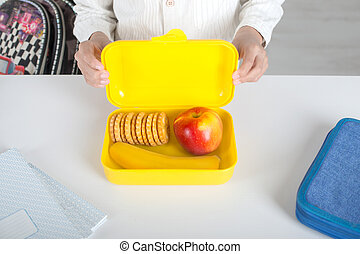 The schoolboy holding a yellow plastic box with lunch. In the box are a banana, apple and a biscuit, there is a pencil box and notebooks nearby