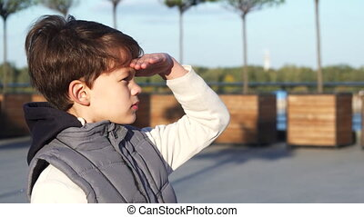 The schoolboy looks through binoculars