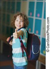 The schoolboy standing near lockers in school hallway.