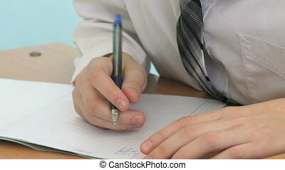 The schoolboy writing the text in the copybook indoors
