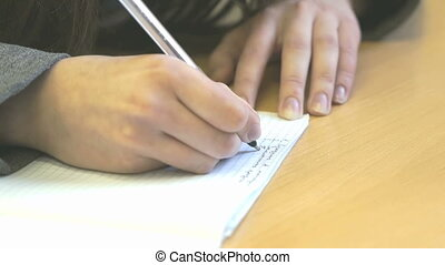 The schoolgirl writing the text in sheet of paper