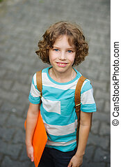 The schoolkid stand on a schoolyard and smiles. The boy has...
