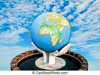 The Sculpture of world in hand on blue sky background