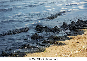 The sea and the beach are polluted with oil. A crude oil spill on the sand of a city beach. Beach oil spill impact, pollution, waste disposal. Ecological catastrophy