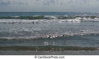 The Sea Waves are Rolling on a Sand Beach in Slow Motion