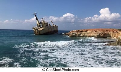 The sea waves beat against the abandoned merchant ship in ...