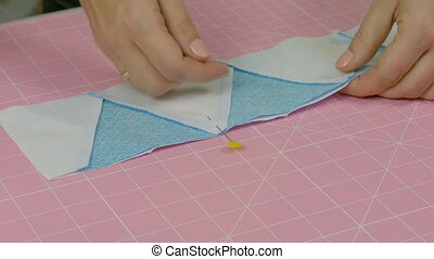 The seamstress connects the cloth with a pin. Do the...