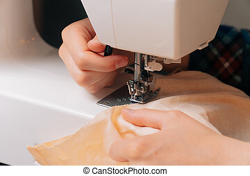 The seamstress lowers the sewing machine's paw down to press the fabric for sewing. Closeup of work on a light background