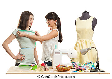 the seamstress takes measurements on the girl the client