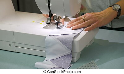The seamstress works on the sewing machine. She makes a...