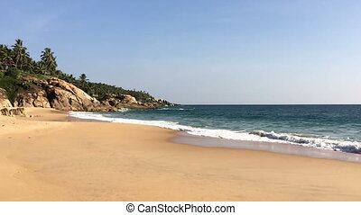 The seashore with stones and palm trees. India. Kerala,
