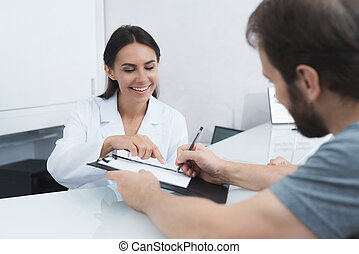 The secretary in a medical clinic helps the patient complete...