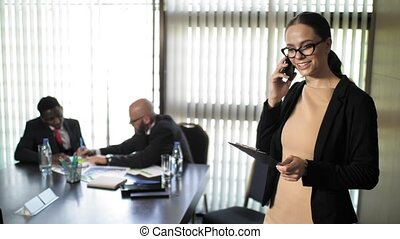 The secretary is talking on the phone during a business meeting of investors in slow motion