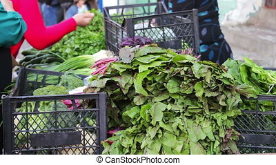 The seller in the market sells greens to buyer. A woman buys fresh vegetables on the market
