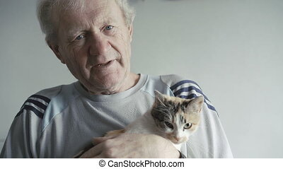 The senior holds cat on hands and talks to it