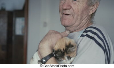 The senior holds cat on hands, caressing it 4K