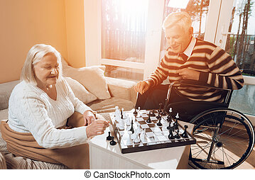 The senior man and woman play chess in the nursing home.