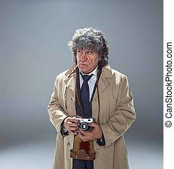 The senior man as detective or boss of mafia on gray studio...