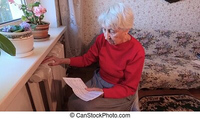 The senior woman holding gas bill in front of heating ...
