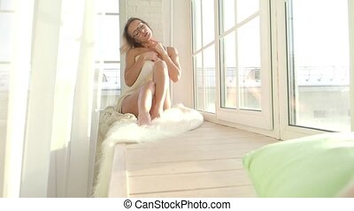 the sensual girl sits on the window in her underwear and touches her body. She's trying to seduce you.