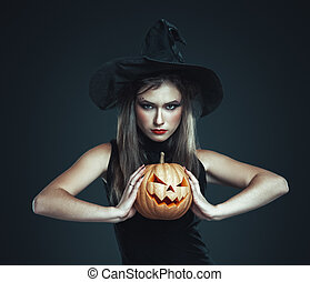 The serious girl is standing with pumpkin