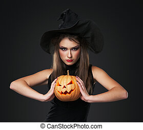 The serious girl is standing with the pumpkin