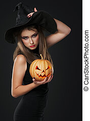 The serious witch is standing with the pumpkin