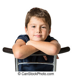 The seven year old boy sits astride a chair - Picture taken...