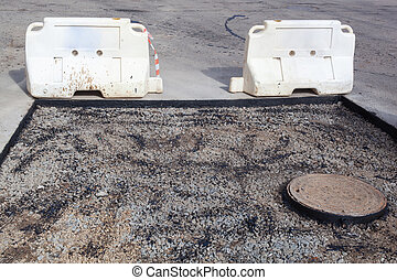 The sewer hatch and pit next to it. Asphalt repair