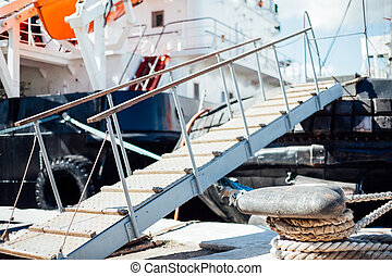 the ship is moored to a dock ladder rope chain