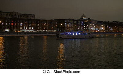 The ship sails on the river at night.