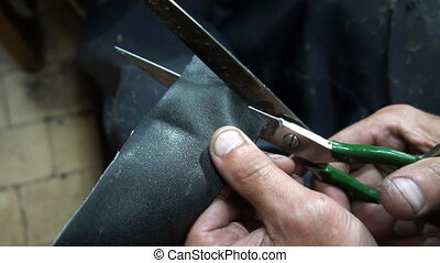 the shoemaker cuts out a patch for shoes.