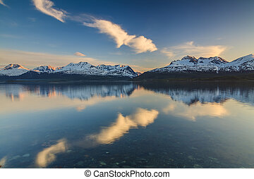 The shore of a mountain lake at sunset