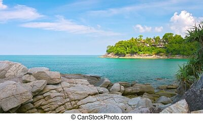 The shore of a tropical sea with rocks. Villas in the background