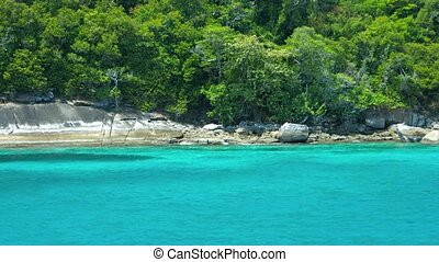 The shoreline of a tropical island with rocks and trees