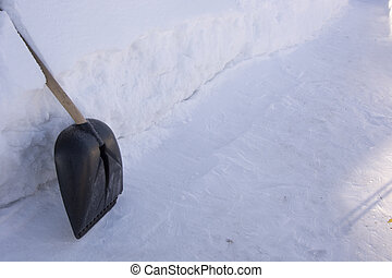 The shovel stands at a high snowdrift. Raking away the snow in the garden. There is a lot of snow in the garden in winter.