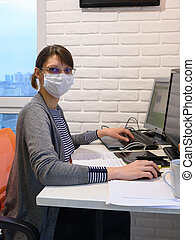 The sick quarantined girl works at the computer, looked into the frame