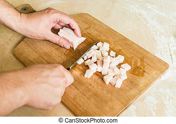 a man cuts raw pork fat into pieces
