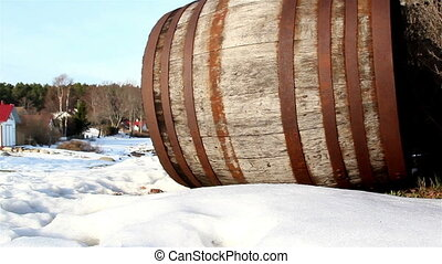 The side view of an old barrel with few grass beside it and...