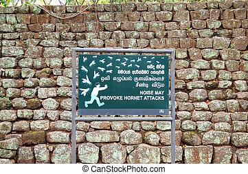 "The sign ""Noise may provoke hornet attack"" in garden near Sigiriya (Lion's rock), Sri Lanka"