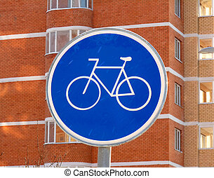 The sign of a cycle track on the background of a brick high-rises