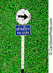 The Sign of  to city on green grass background