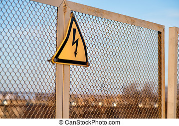 The sign warning about danger of electricity on a metal fence