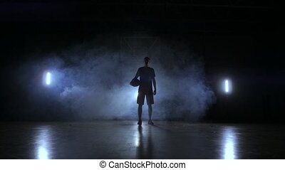 The silhouette of a basketball player on a dark background with smoke on the basketball court throws a basket ball and look at the camera in slow motion