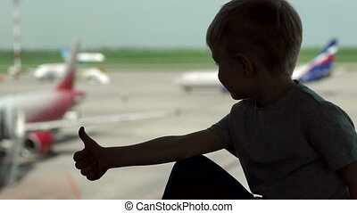 The silhouette of a little boy near window at the airport, he shows his thumb up