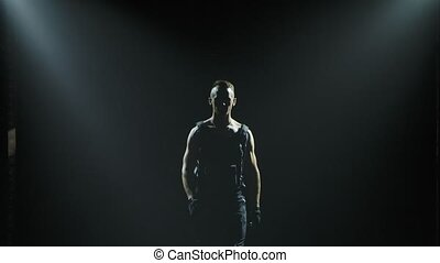 The silhouette of a muscular man looms out of the darkness and smoke. A man of athletic physique posing in a dark studio. Close up in slow motion