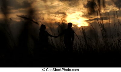 The silhouette of a pregnant woman with her husband in a field at sunset.