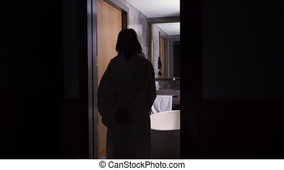 the silhouette of a woman, she comes out of the bathroom in...